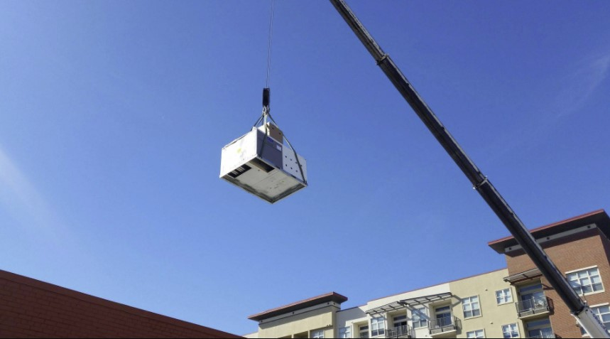 A crane lifting an air con unit on to the top of an apartment.