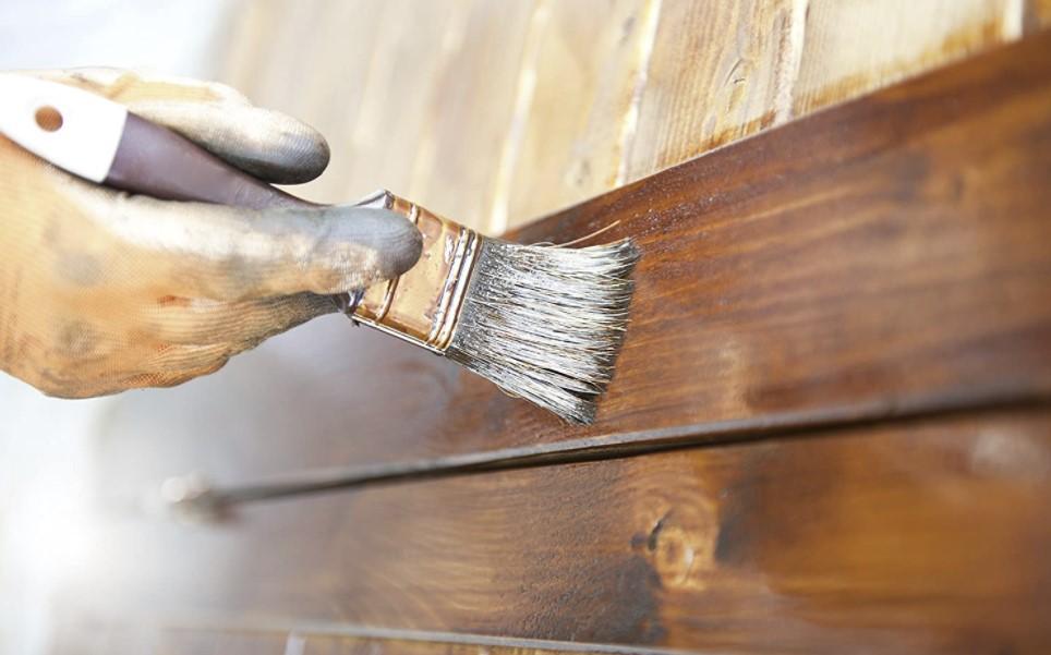 A person applying varnish